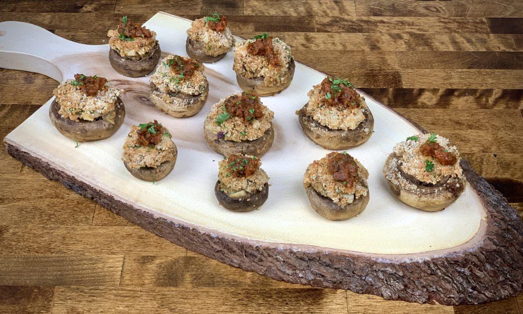 Vegan crab stuffed mushrooms on a display cutting board.